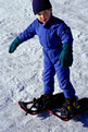 young boy trying snow shoes